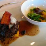Braised beef on polenta square with mushroom, crispy pig, vegetables and black truffle